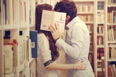 pareja besandose detrás de libro